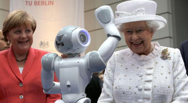 The Queen laughs as she watches a robot with Chancellor Angela Merkel at a Berlin university