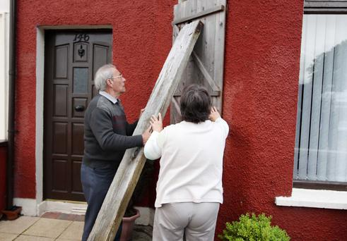 Woodvale Road residents board up their houses yesterday after three nights of violence
