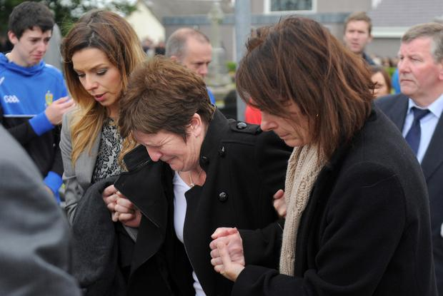 Aaron Devlin's mother Carmel (centre) breaks down during the funeral for the GAA star