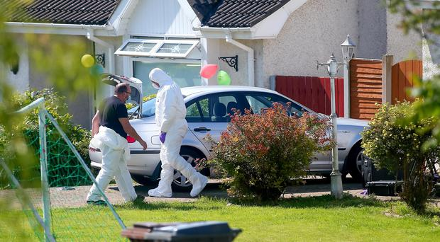 Police officers investigating the murder of Kevin McGuigan search a property in the Lagmore area of west Belfast
