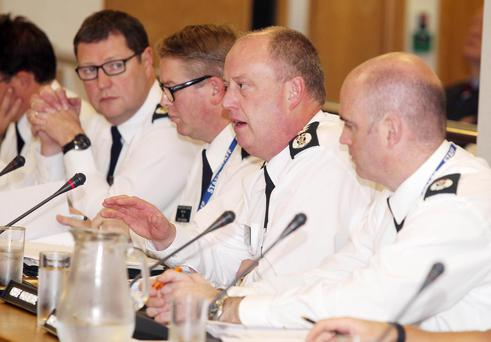 PSNI Chief Constable George Hamilton (second from right) takes questions from the Policing Board during their meeting yesterday at the organisation's offices in Clarendon Dock, Belfast