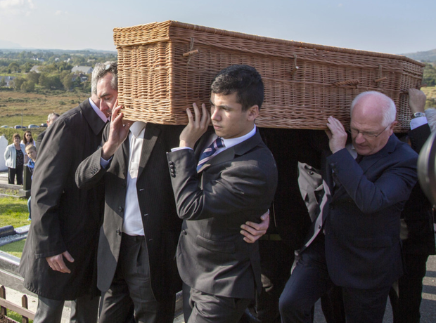 Family and friends carry the remains of playwright Brian Friel to the graveside