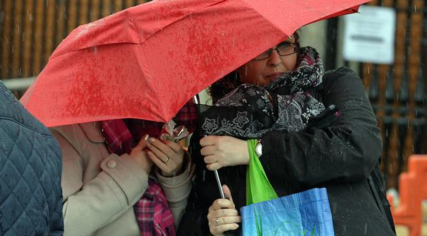 Shoppers struggle to keep control of an umbrella