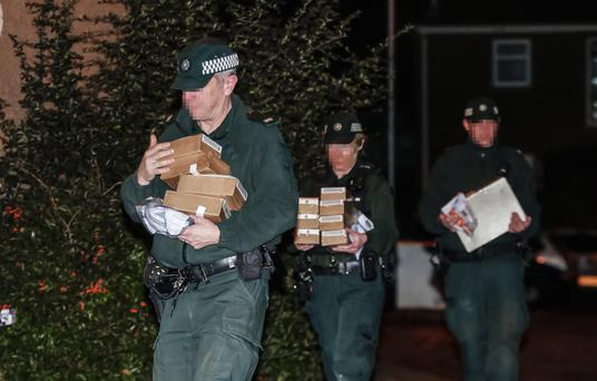 Police officers removing a large quantity of items from a property in Poleglass