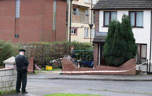 A police officer outside the house in Rossnareen Avenue in west Belfast where a man was shot in the head