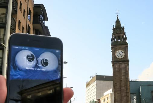 Telegraph photographer Kevin Scott with his phone showing 3.05pm, while the Albert Clock is stuck at 11.21