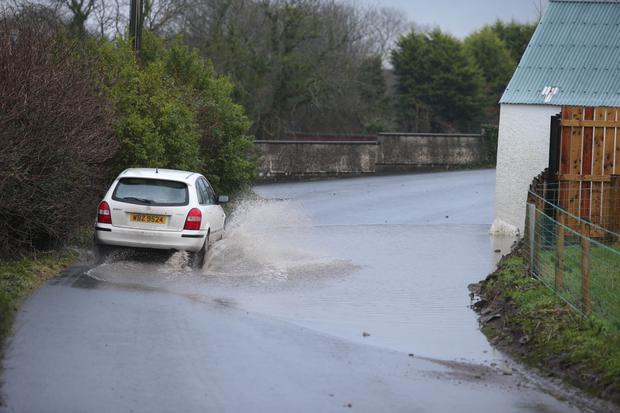 A motorist drives through floodwater near Moneyrea, Co Down