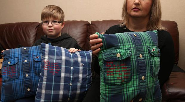 Donna Hanna and son Luke hold cushions made from shirts worn by Robert Hanna for each of his three children