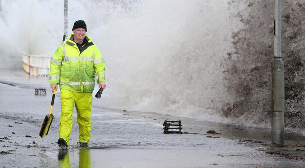 A workman tries to clear drains in the coastal village of Carnlough as waves crash over the sea wall yesterday