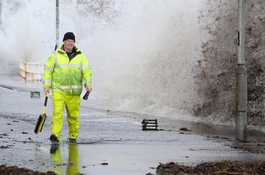 A workman tries to clear drains in the coastal village of Carnlough as waves crash over the sea wall