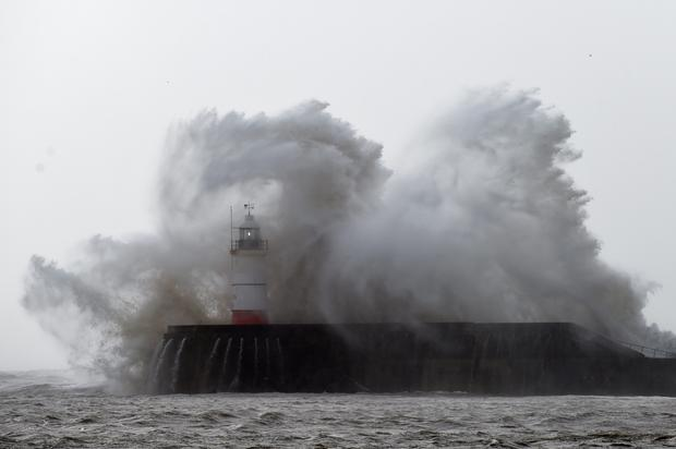 Waves crash over the harbour wall at Newhaven