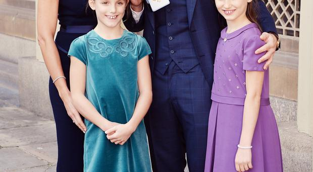 The couple with his daughters Isla and Luna receiving his OBE at Buckingham Palace