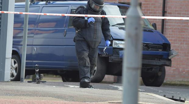 A bomb disposal unit officer inspects the damaged van after a car bomb attack on a prison officer at Hillsborough Drive.
