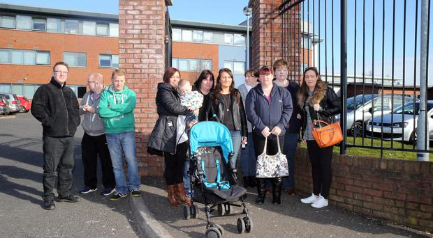 Concerned parents of pupils at De La Salle College outside the school gates yesterday