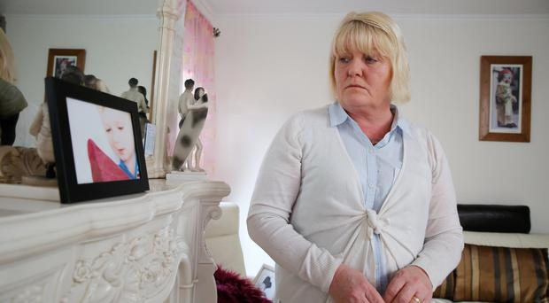 Debbie Johnston looking at a photo of her son Brodie in her east Belfast home