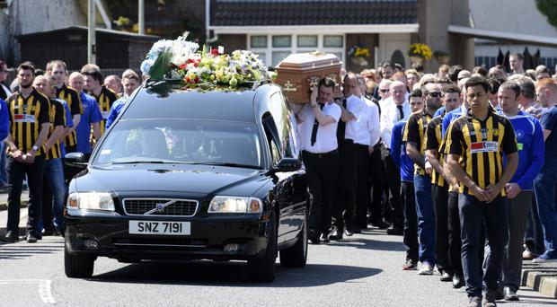 Players from Ardmore GAC and Nierin FC form a guard of honour at the funeral of Gerard Quinn