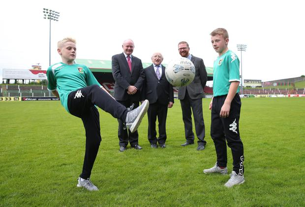 President of Ireland, Michael D Higgins with deputy First Minister Martin McGuinness, Economy Minister Simon Hamilton, and junior players Charlie Lindsay and Aaron Wightman at The Oval