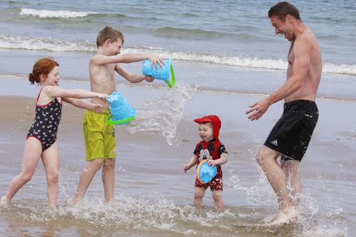 A family enjoys splashing around at Whiterocks beach, Portrush