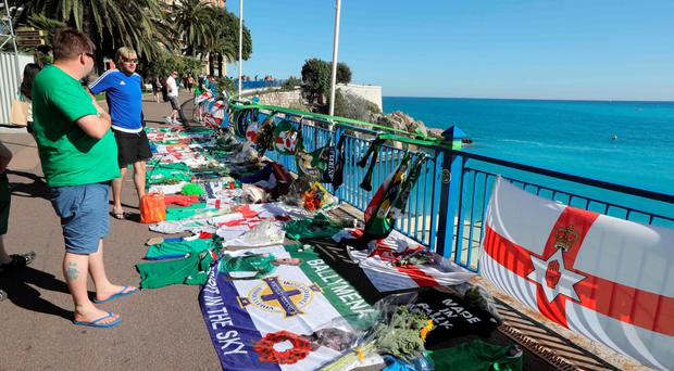 Northern Ireland fans stand at the promenade where Darren lost his life