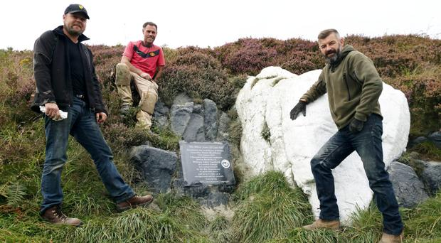 Christopher McLaughlin, Patrick McAdams of McAdams Memorials and Lee Jones at the plaque installed on the White Stone on Cave Hill