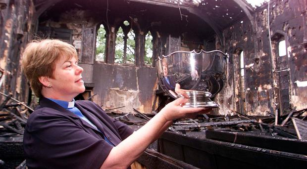 The Rev Dr Liz Hughes holds up a rose bowl that survived the arson attack on her church