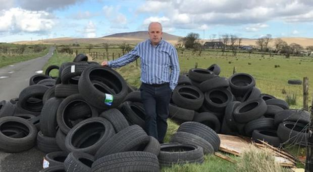 James Tinsley with tyres dumped in Lisburn