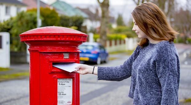A woman posts a letter in the King George V cast iron post box located at Bristow Park, Belfast