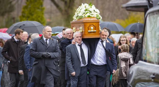 Pallbearers carry the coffin of Reggie Donnelly