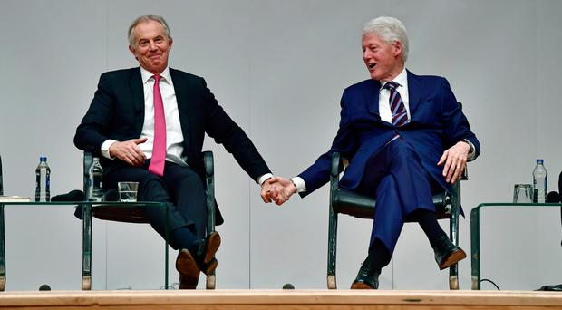 Former British Prime Minister Tony Blair and ex-US President Bill Clinton grasp hands with one other as they attend an event to mark the 20th anniversary of the Good Friday Agreement at Queen's University
