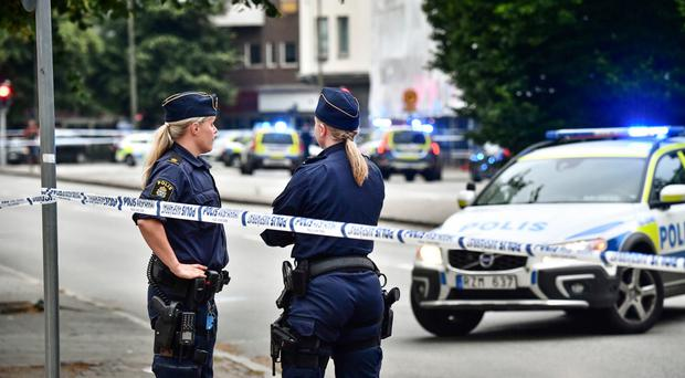 Police stand next to a cordon in central Malmo, Sweden