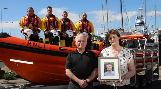 Bangor lifeboat crew look on while Billy and Brenda Coates show a picture of their son William, who drowned on holiday, as the RNLI launched its national drowning prevention campaign yesterday