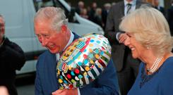 The Prince of Wales holds a birthday gift as he and the Duchess of Cornwall arrive for a tea party at Spencer House