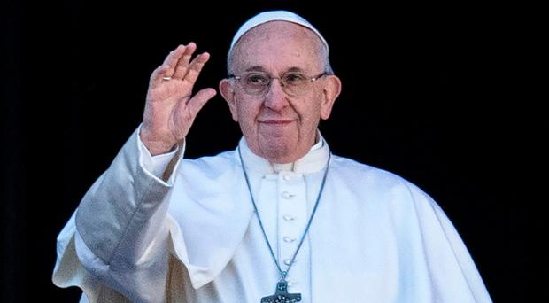 Pope Francis waves from the balcony of St Peter's basilica