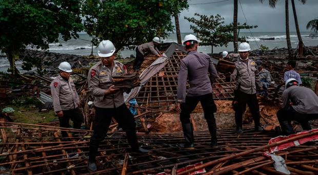 Indonesian police clear the ruins of a house