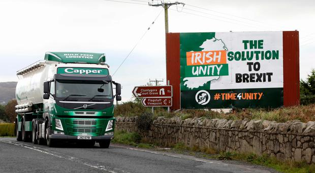 A lorry passes an anti-Brexit billboard at the border
