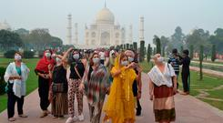 Foreign tourists wearing face masks visit the Taj Mahal under heavy smog conditions