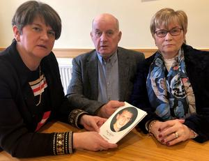 DUP leader Arlene Foster with Breege and Stephen Quinn and a photograph of their murdered son Paul
