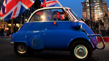 A man waves Union flags from a small car as he drives past Brexit supporters in Parliament Square