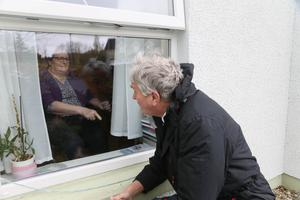 Jim Wells talks to his wife Grace through a window at her care home