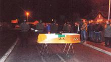 Masked CIRA gunmen fire shots over the coffin of Liam Mulhern