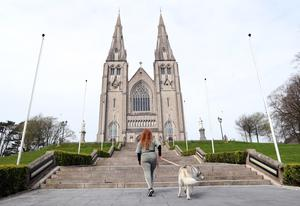A dog walker at the steps of a quiet St Patrick's Cathedral in Armagh
