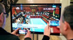 Journalists watch a live feed of the restored Assembly