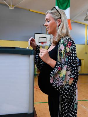 A pregnant woman votes in Dublin