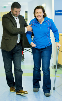 Clodagh Dunlop leaves hospital on her own two feet, with a helping hand from her partner Adrian Campbell