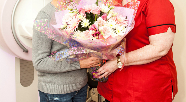 Angela Maxwell from Dunmurry receives a bouquet from Action Cancer's Joanna Currie after she was the 10,000th woman to be screened for breast cancer by the charity in 2014-15