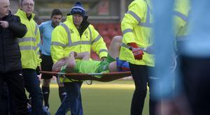 Ryan Catney being carried off the pitch after sustaining a fracture