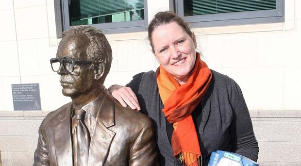 Lynda Donaldson beside a statue in Lisburn of Professor Frank Pantridge, the Northern Ireland-born inventor of the portable defibrillator