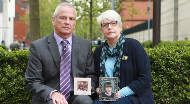 Alan and Jennifer Roberts hold pictures of daughter Claire outside court
