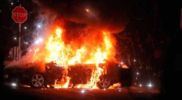 A car burns in Creggan after petrol bombs were thrown at police