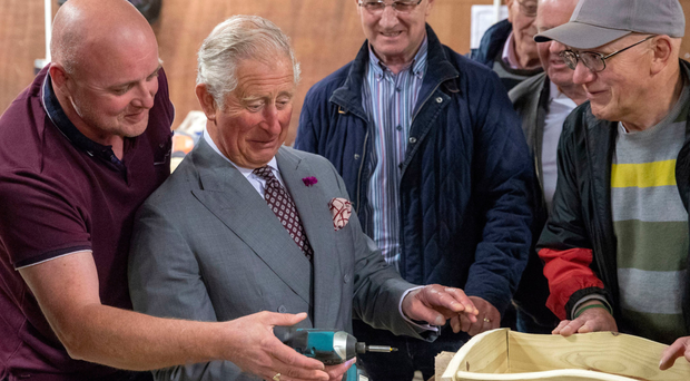 The Prince of Wales uses an electric screwdriver during a visit to the Owenkillew Community Centre in Gortin